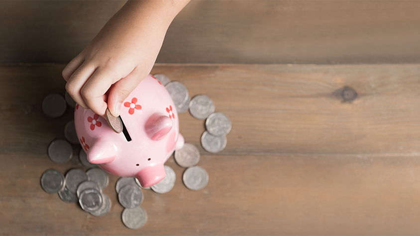 hand of little kid putting coins in pink piggy bank