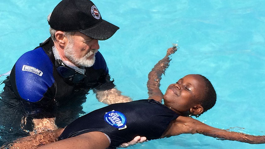 Boy in pool being helped by swimming instructor