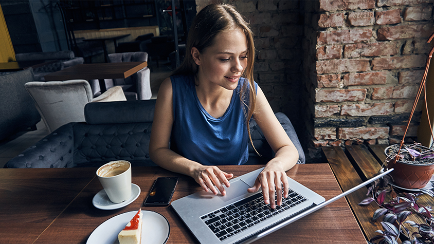 Young woman working on her laptop while drinking coffee and eating a piece of cake.
