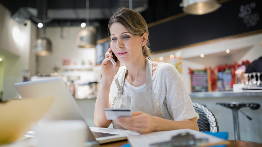 woman on a phone while doing online purchase with a credit card in her hand