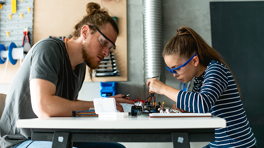 instructor working with student to build electronic device
