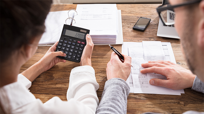 Close up of couple calculating finances on a wooden table.
