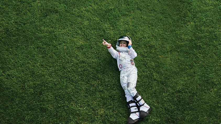 little girl laying down on lawn in astronaut dress