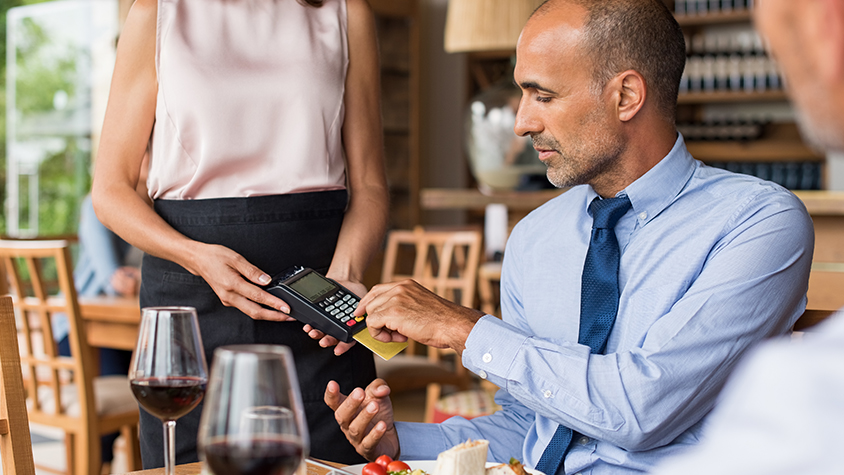 A businessman pays the waitress with his credit card at a restaurant.