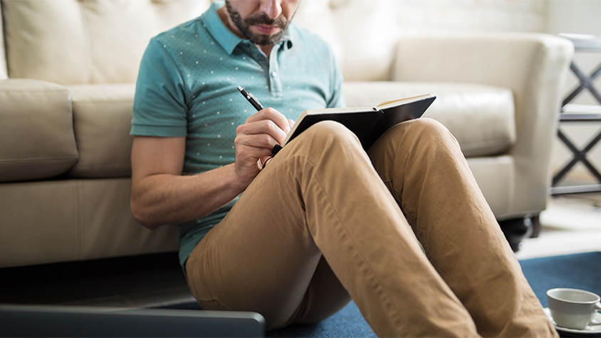 A man writes in his notebook while sitting on the floor against a couch in his living room.