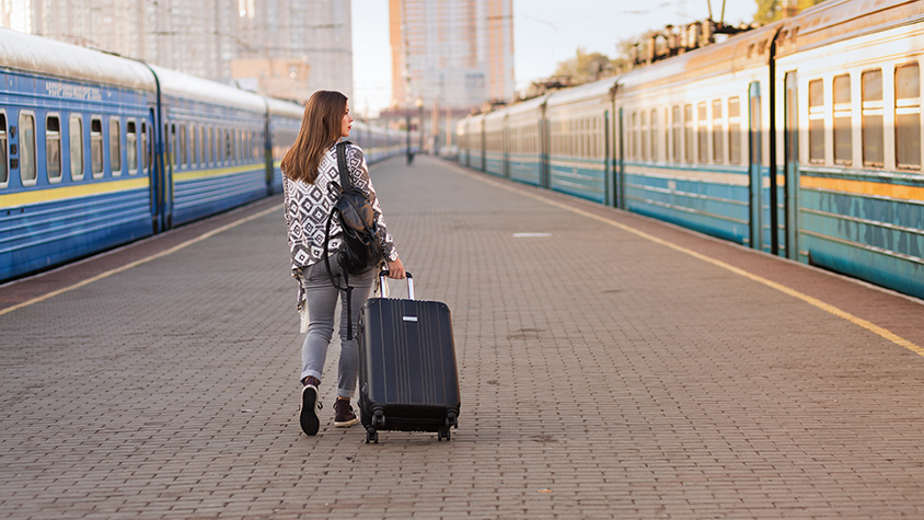 woman walking with luggage on train station