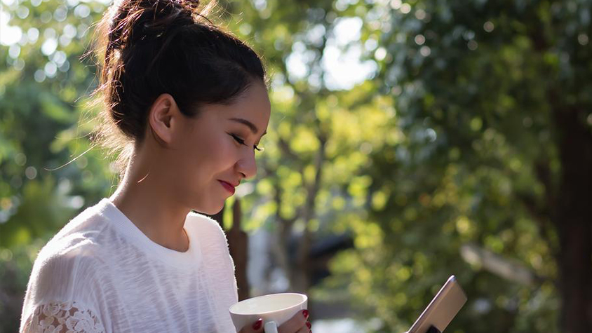 Attractive woman smiling, holding coffee and looking down at phone outside