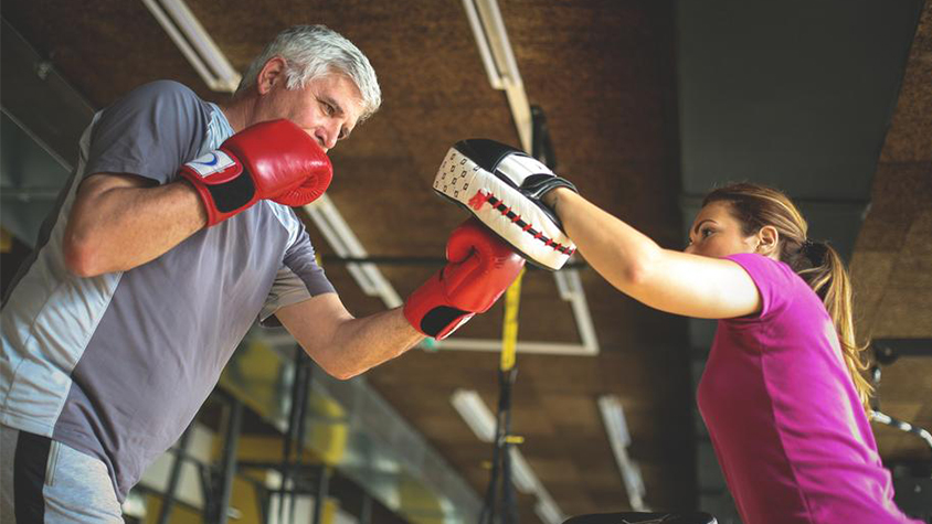 A mature male is shown in a boxing studio working with a younger woman trainer.