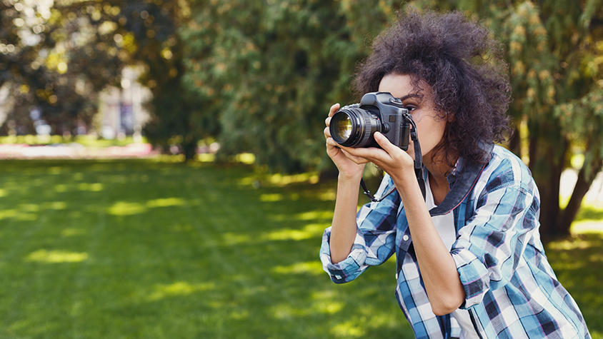Black young female focuses her camera to take a photo outside.