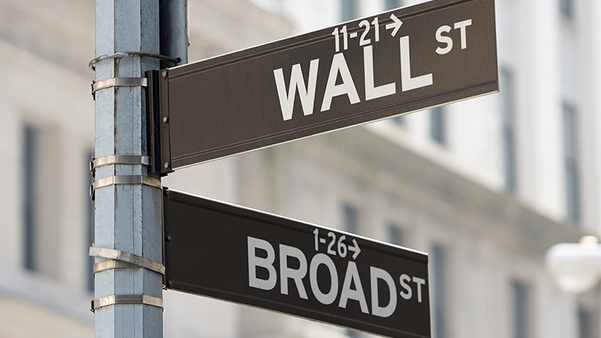 Street sign showing wall street and broad street