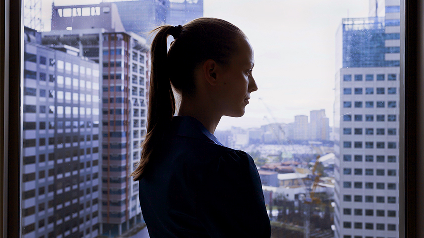 woman in highrise building looking out from window