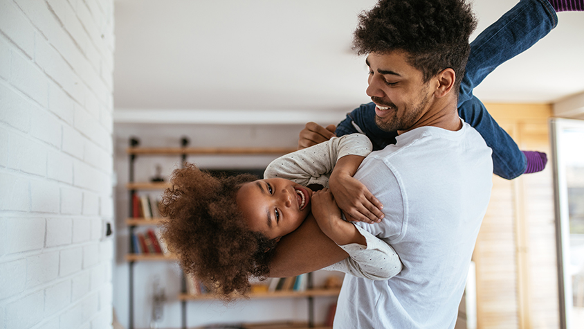 African American father playfully holds his daughter, laughing.