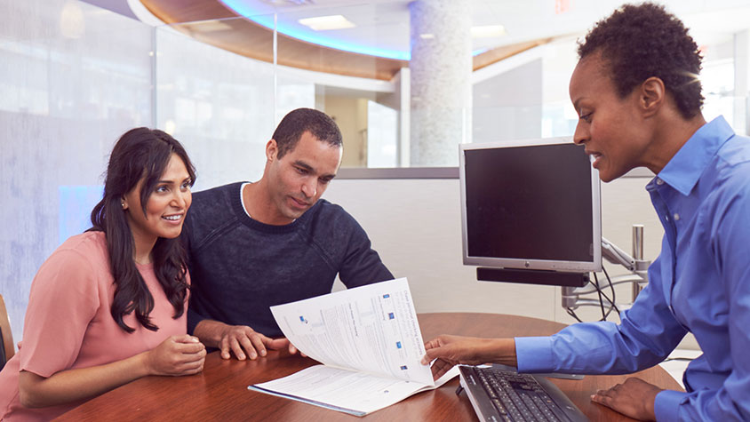 man and woman sitting at desk looking at paperwork with financial advisor