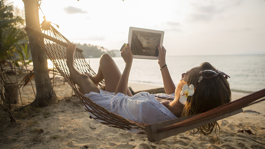 Woman in a hammock reading by the beach