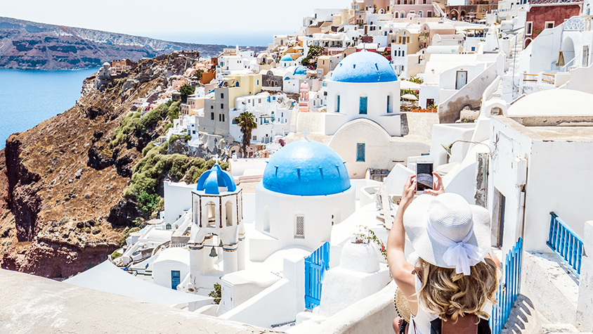Woman stops to take photo on stairs in Santorini, Greece