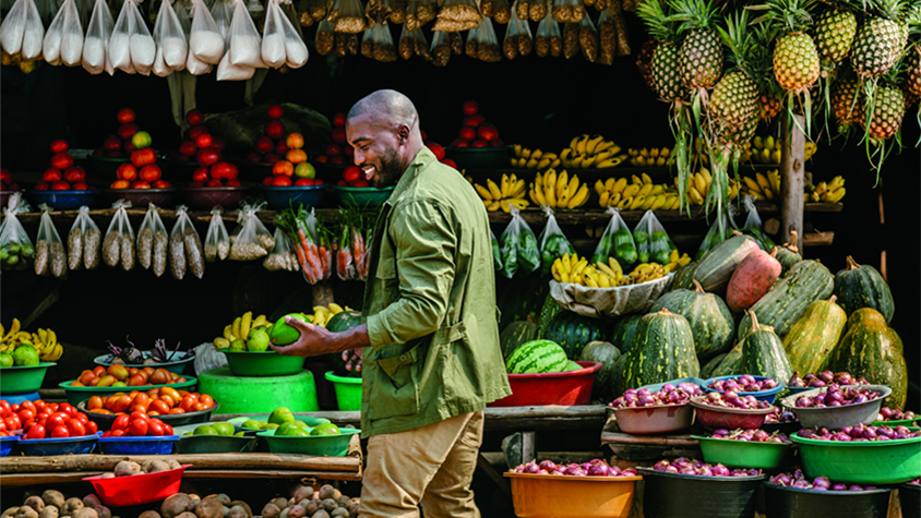 Man holds a piece of fruit while shopping at a food stall in Uganda.