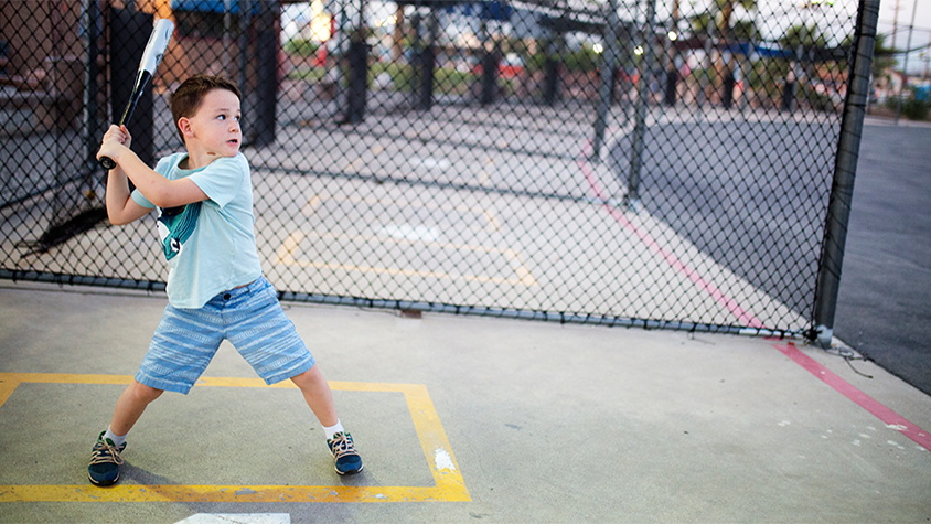 Young boy winds up to swing a baseball at a batting cage.