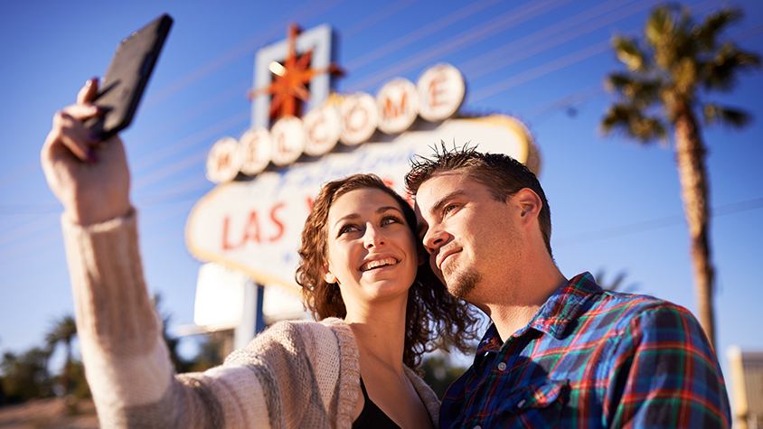 couple taking a selfie in front of Las Vegas iconic sign