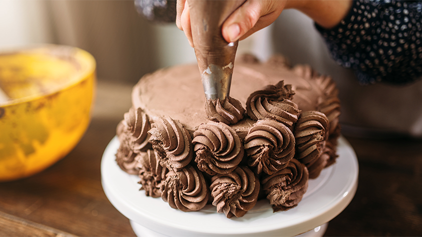 Close up image of hands frosting a cake
