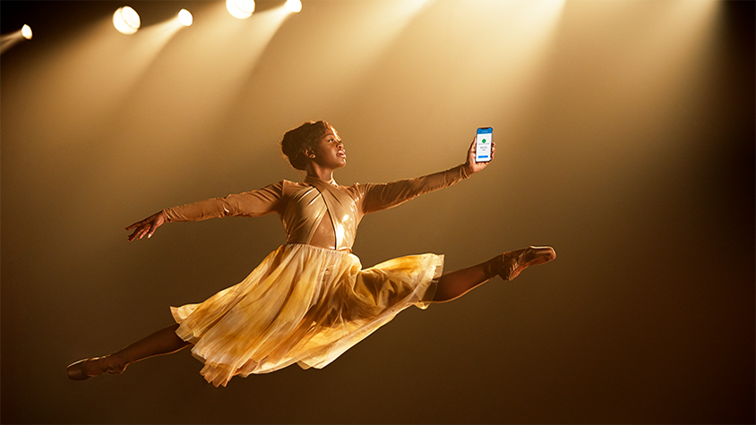 Young African American woman in ballerinas costume on stage using Chase Pay on smartphone while taking a big leap in the air.