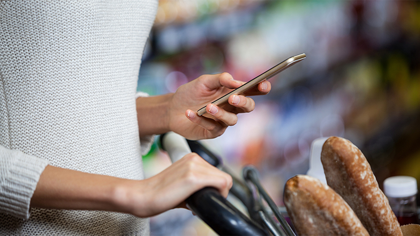 woman with shopping cart looking at smartphone