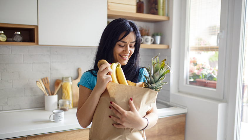 Young hispanic woman stands in kitchen smiling while holding a brown bag full of fresh fruit.