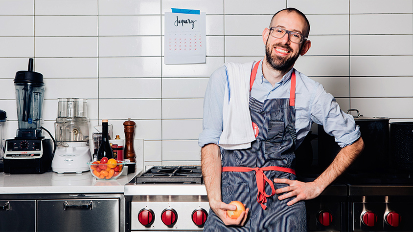 Photo of David Tamarkin, Digital Director at Epicurious, standing in a kitchen with an apron on.