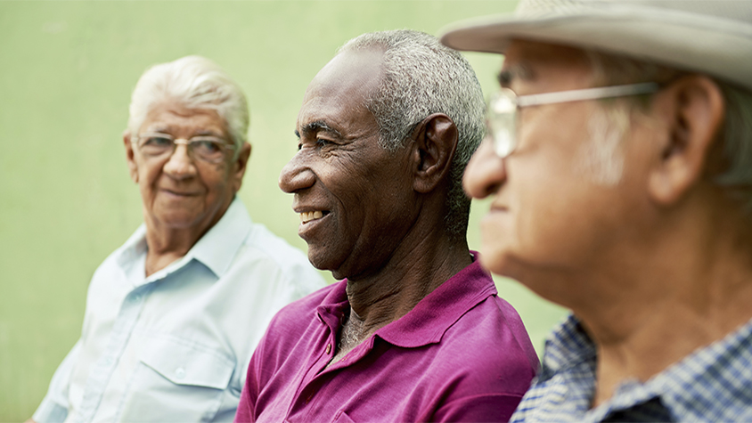 Three elderly men of different ethnicities sit on a bench in the park talking.
