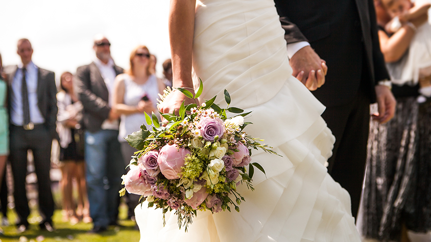 Bride holding flower bouquet standing with groom