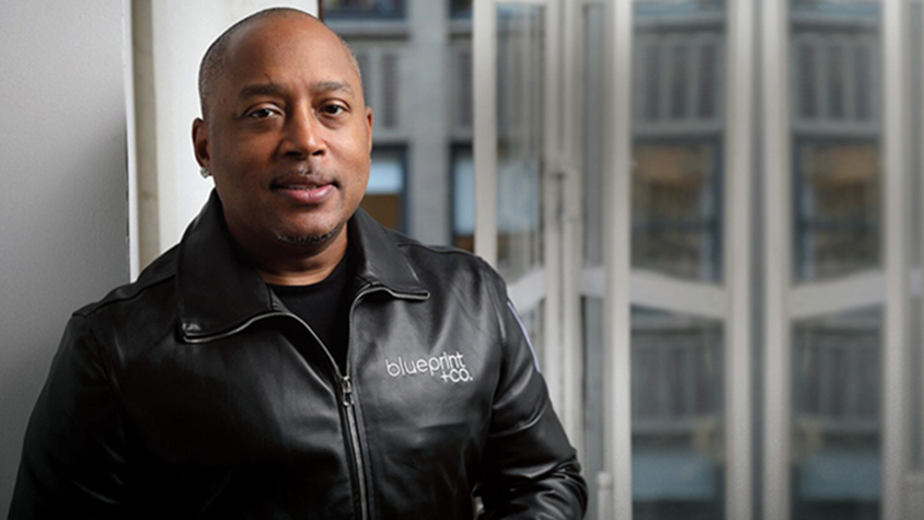 Portrait of Daymond John in a black leather jacket.