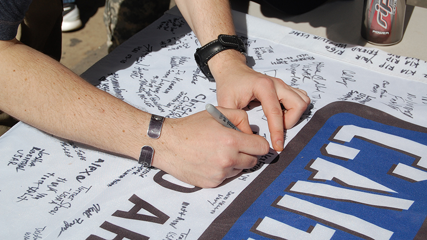 person siging on Carry the Load banner