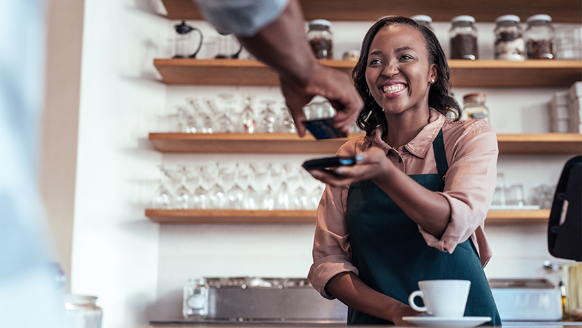 coffee shop employee taking credit card from customer