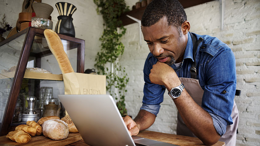 african american male looking at laptop in his bakery shop