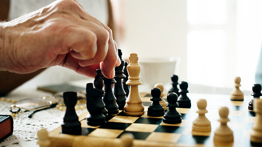 Close-up of a chess board that elderly person is participating in.
