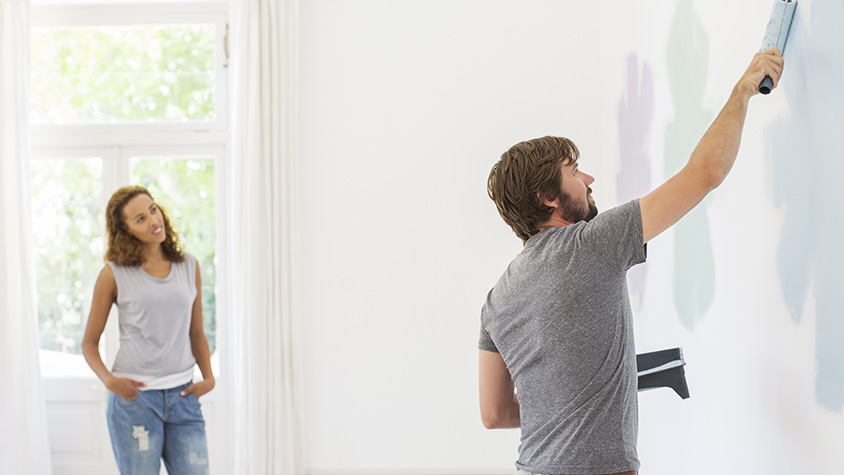 Man painting wall with girlfriend observing