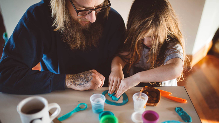 A father and daughter sit at a wooden table and play with play-doh.