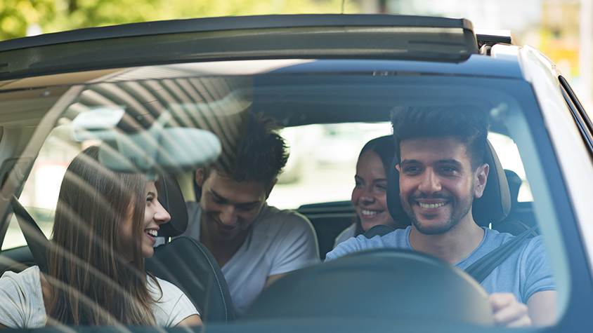 A young male drives his car with three friends.