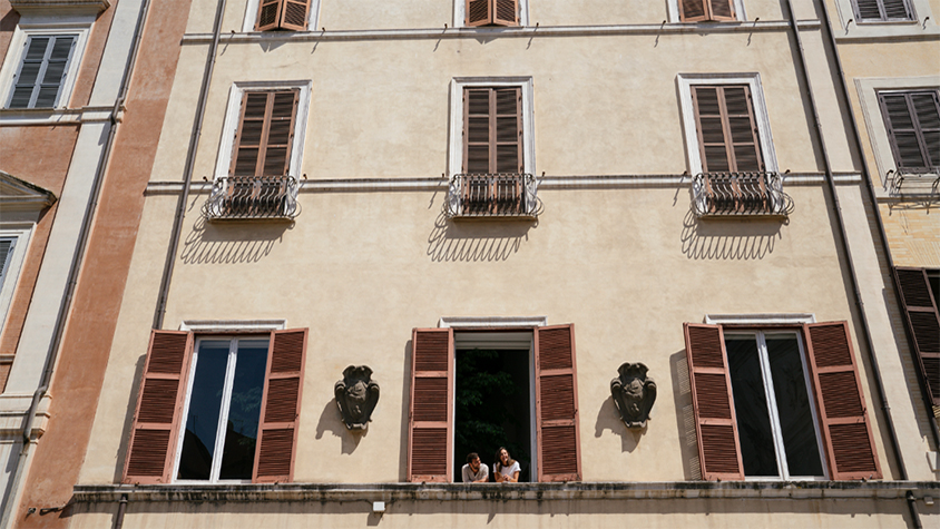 A couple looks out of a window from an old building in Rome, Italy.