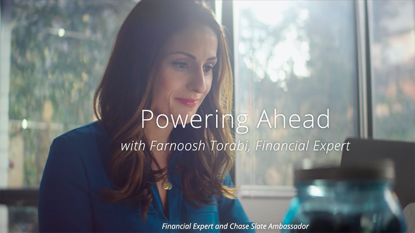 Farnoosh Torabi sits at a table in her house while typing on her laptop.