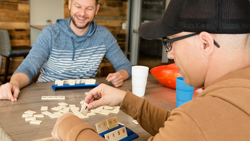 John Schneider and David Auten sit at a wooden table while playing a board game.