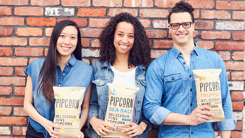 A shot of the three Pipcorn founders holding up a bag of their snack food products.