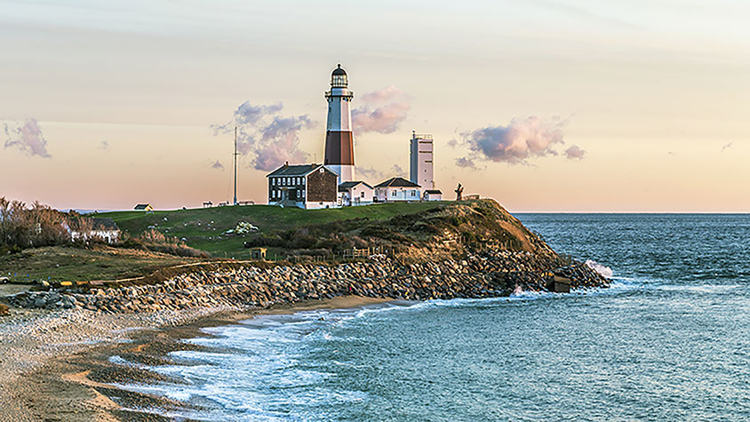 A landscape view of Montauk, including a beach and lighthouse scene at sunset.