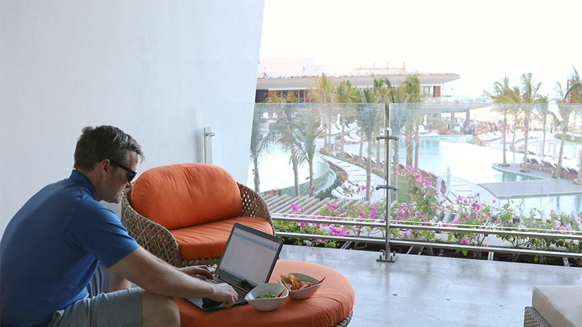 Pete Reese, a middle-aged Caucasian man, works on his balcony at a oceanfront resort.