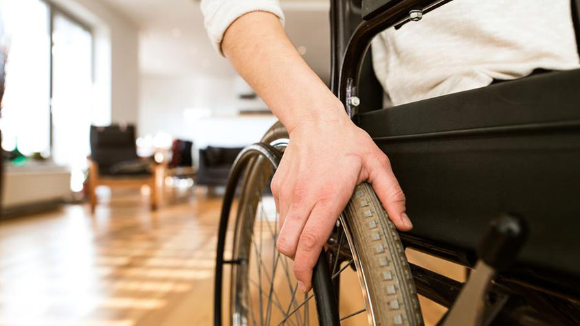 Close-up image of a hand on a wheelchair wheel in a home's living room.