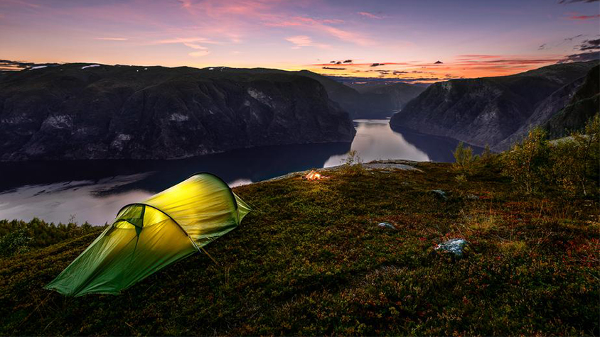 A bright yellow-green tent is shown on the cliff of a mountain, with a sunset in the background.