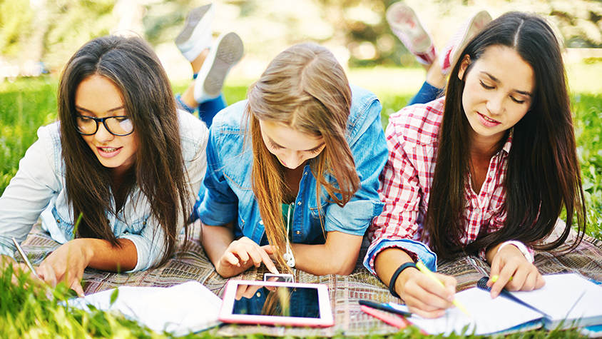3 girls studying on lawn