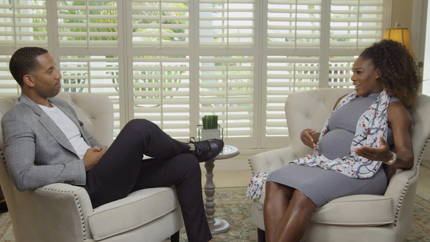 Serena Williams and Maverick Carter sit across from each other in white chairs in a living room of a house.