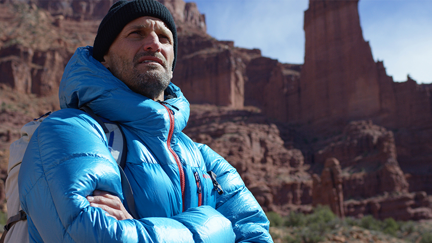 Chris Burkard is shown standing near the red rocks of Moab in a blue windbreaker.