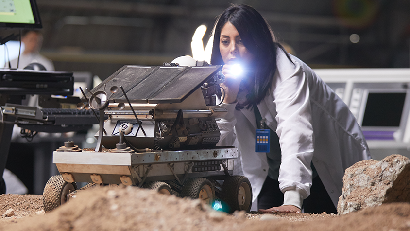 Scientist Diana Trujillo is on her knees while examining new rover technology for exploring mars.