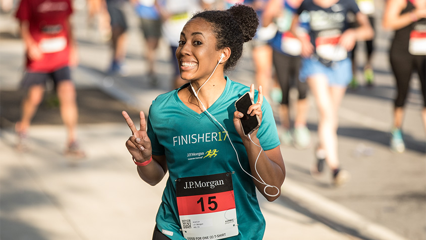 A female runner taking part in the JPMorgan Corporate Challenge smiles at the camera.